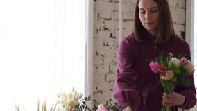 Woman florist gathering bouquet in flower shop stock video footage