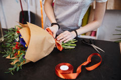 Woman florist making bouquet of flowers using red ribbon Stock Photo