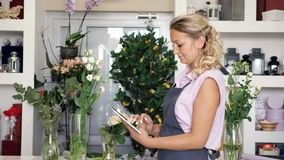 Woman florist seller is working on tablet in flower shop, side view. Blonde woman in uniform takes online order for flower bouquets from buyers. Woman florist stock video