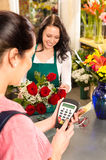 Woman florist selling flowers customer paying card. Woman florist selling flowers customer paying credit card red roses Royalty Free Stock Photos