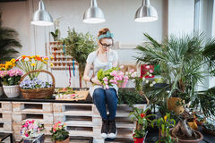Woman florist sitting and arranging pink tulips in flower shop. Cute lovely young woman florist sitting and arranging pink tulips in flower shop stock image