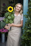 Woman florist standing at the entrance to her shop, holding a sunflower Stock Photos