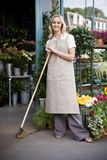 Woman florist standing at the entrance to her shop, leaning on a broom Stock Images
