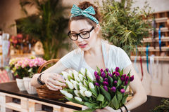 Woman florist taking care of tulips in flower shop Stock Photo
