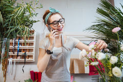Woman florist talking on cell phone in flower shop Stock Photography