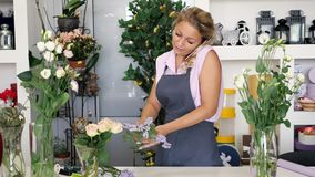 Woman florist talks on phone and makes a bouquet working in flower shop.