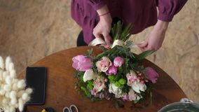Close-up of female hands tied in bow ribbon on bouquet stock video footage