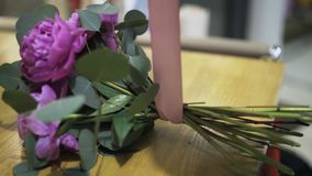 Woman florist tying purple flower bunch with a pink ribbon stock video