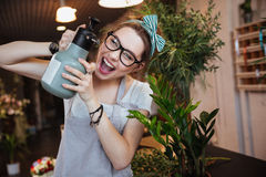 Woman florist with water sprayer watering flowers and shouting Royalty Free Stock Photo