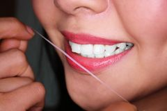 Woman flossing her teeth. Woman flossing her own teeth by dental floss Stock Photo