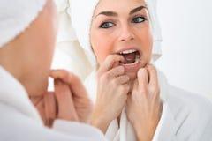 Woman flossing teeth Stock Image