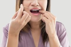 Woman flossing teeth with dental floss stock photo