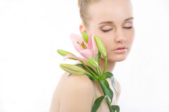 Woman with a flower. Woman with eyes closed with a pink flowers on shoulder Royalty Free Stock Image