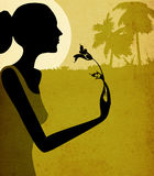 Woman with flower. Grunge design, woman smelling a flower in moonlight Stock Image