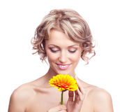 Woman with a flower. Beautiful young blond curly woman with a flower in her hands Royalty Free Stock Image