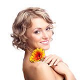 Woman with a flower. Beautiful young blond curly woman with a flower in her hands Stock Images