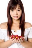 Woman And Flower. An attractive young Asian woman in white top holding red flowers on white background Stock Image