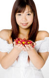Woman And Flower. An attractive young Asian woman in white top holding red flowers on white background Stock Photos