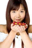 Woman And Flower. An attractive young Asian woman in white top holding red flowers on white background Stock Photography