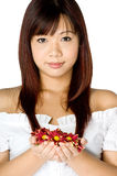Woman And Flower. An attractive young Asian woman in white top holding red flowers on white background Stock Photo
