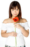 Woman And Flower. An attractive young Asian woman in white top holding a red flower on white background Royalty Free Stock Images