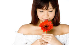 Woman And Flower. An attractive young Asian woman in white top holding a red flower on white background Royalty Free Stock Photography