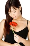 Woman And Flower. An attractive young Asian woman in white top holding a red flower on white background Stock Image