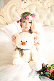 Woman with Flower Arrangement. Beautiful Woman with Flower Arrangement, Flower Wreath, Makeup and Handmade Toy lying in Bed Stock Photos