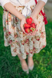Woman in flower dress holding a bunch of strawberries royalty free stock photo