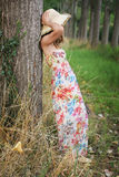 Woman with flower dress leaning to a tree Royalty Free Stock Photos