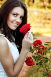 Woman in flower garden smelling red roses stock photo