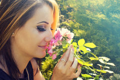Woman in flower garden smelling roses Stock Photos