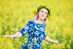 Woman with flower garland at yellow rape seed meadow. Young woman in colorful dress with flower garland at yellow green rape seed meadow Royalty Free Stock Photo