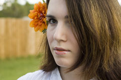 Woman with flower in hair. Thoughtful young woman with orange flower in long brunette hair Stock Photography