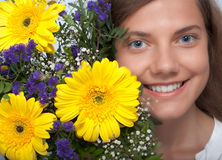 Woman flower happiness. Young woman with bouquet of flowers beside her face stock image