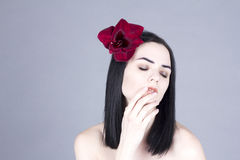 Woman with a flower in her hair touching the mouth with eyes closed Royalty Free Stock Photo
