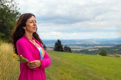 A woman with a flower in her hand Stock Image
