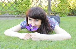 Woman with flower lying on the grass Stock Photos