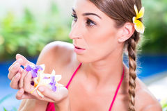 Woman with flower petals in tropical garden at pool Stock Photography