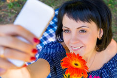 Woman with flower photographing himself Royalty Free Stock Photo