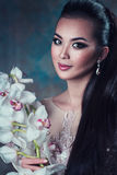 Woman with flower portrait. Young asian woman with orchid flower portrait Royalty Free Stock Photo
