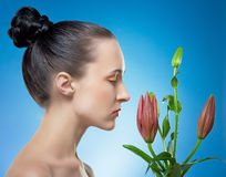 Woman with the flower by red lily. Royalty Free Stock Photography