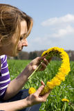 Woman with flower wreath. Woman weaves a wreath of dandelion flowers Royalty Free Stock Images