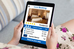 Woman in flowered dress holding tablet with app hotel booking Stock Photos