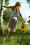 Woman with flowers. Young woman holding sunflowers by the tree Royalty Free Stock Photography