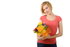 Woman with flowers. A young woman in casual clothes stands with a bouquet of colorful flowers in her hands. Isolated on white background Stock Image