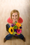 Woman with flowers. Young woman in casual clothes sits on a stool with a bouquet of colorful flowers in her hands. Hardwood floors are in the background Stock Images