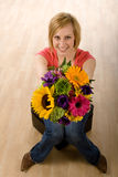 Woman with flowers. Young woman in casual clothes sits on a stool with a bouquet of colorful flowers in her hands. Hardwood floors are in the background Royalty Free Stock Images
