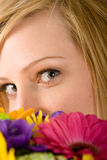 Woman with flowers. Close-up of a young woman's eyes as she peeks behind a bouquet of colorful flowers Royalty Free Stock Photography