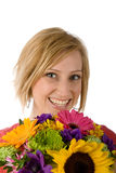 Woman with flowers. Portrait of a beautiful blond woman with colorful flowers in the foreground. Isolated on a white back ground Stock Images
